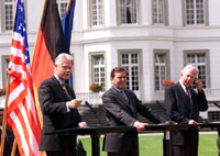 President Clinton, Chancellor Schroeder, and President of the European Union Jacques Santer hold a press conference on the lawn outside of the Palais Schaumburg.