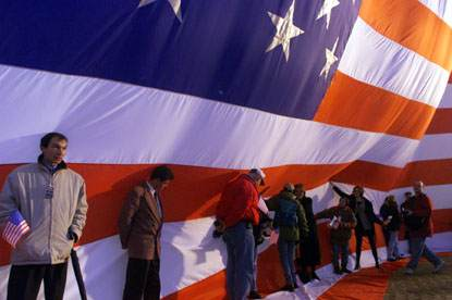 On a very windy day, a group attempts to secure the American flag as they wait for President Clinton to give a speech.