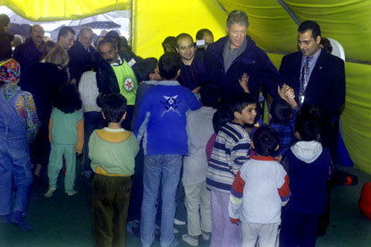 Young children gather around President Clinton inside a tent at the camp.