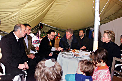 The President and First Lady are invited into a tent for a cup of tea.